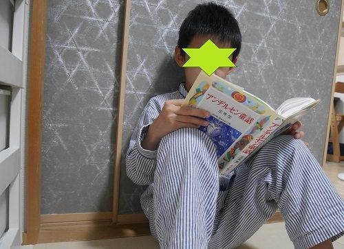 アンデルセン童話3年生の本を読んでいる小学生の男の子