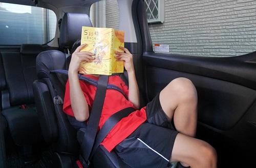 車の中で読書をする小学5年生の男の子