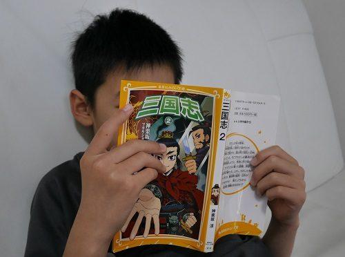 集英社の「三国志」を読む小学生の男の子