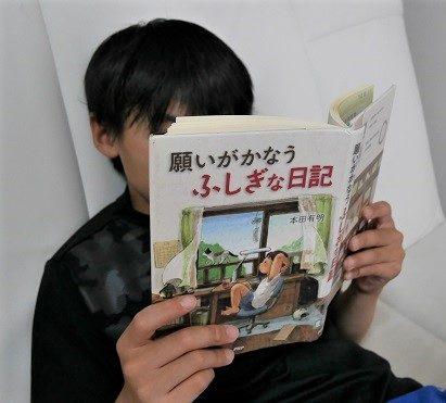「願いがかなうふしぎな日記」の表紙とそれを読む小学生男子