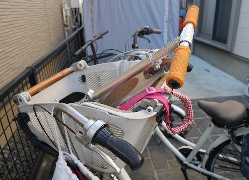 子供乗せ自転車の前かごにキックボードを入れているところ