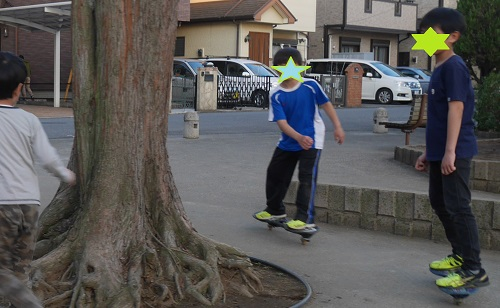 公園で小学生男子たちがキックボードで遊ぶ