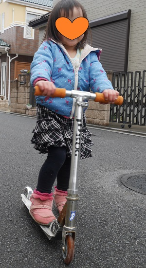 キックボードをこぐ3歳の女の子