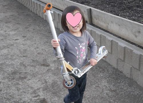 キックボードで遊ぶ4歳の女の子