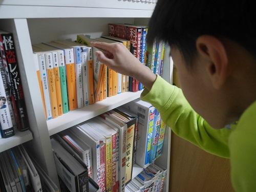 東野圭吾の小説を読む小学生の男の子