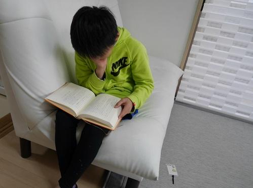 ソファに座って夢中で「モモ」を読む小学生の男の子