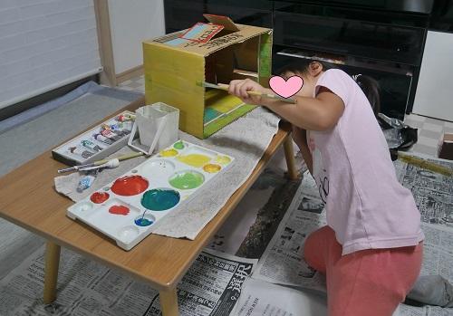 段ボール工作で絵の具で色を塗る女の子