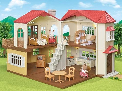 赤い屋根の大きなお家に家具と人形を入れて遊んでいるところ