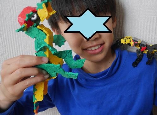 緑の恐竜ラキューを肩にのせている小学生の男の子
