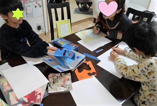 しかけ絵本で創作の立体カードを工作する子供