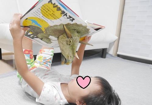 とびだす図鑑 恐竜のトリケラトプスのページを見ている4歳女の子