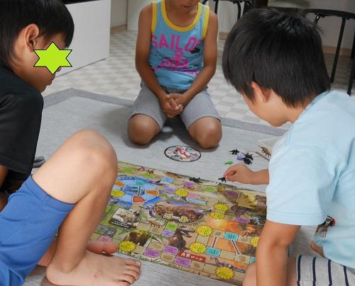 恐竜ボードゲームで遊ぶ小学生男の子3人
