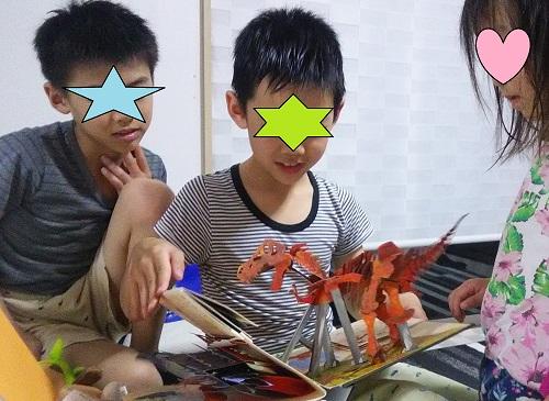 恐竜時代のしかけえほんを見ている兄弟の子供3人