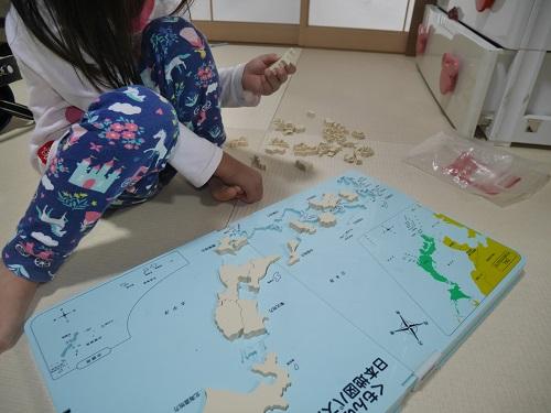 くもんの日本地図パズルの発展ピースをする4歳の女の子