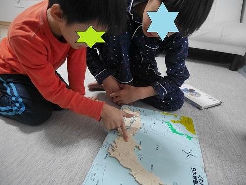 くもんの日本地図パズルの発展ピースを見て話す子供2人