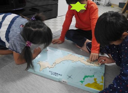 くもんの日本地図パズルで遊んでいる兄弟3人