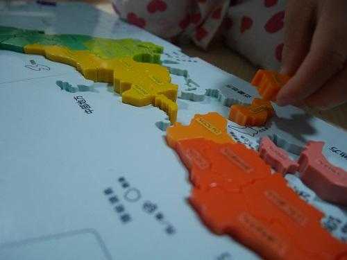 くもんの日本地図パズルで段差にピースをはめこんでいる手
