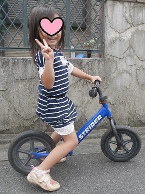青のストライダーに乗っている4歳の女の子