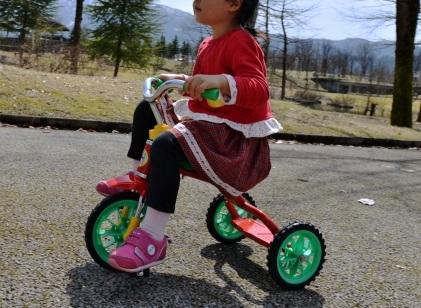 三輪車に乗る3歳女の子