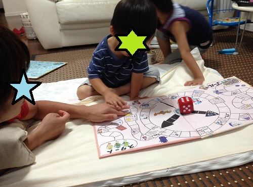 手作りすごろくで遊ぶ3歳の子供と親