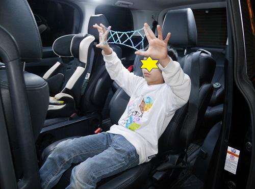 車の座席であやとりで遊ぶ小学生男の子