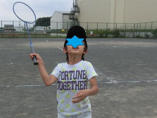 公園でバドミントンをして遊んでいる小学生男の子