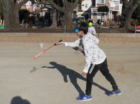 公園でバドミントンをして遊んでいる小学生男子