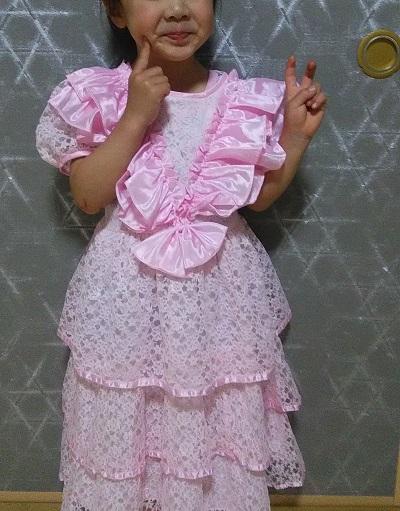ピンクのドレス姿でにっこり笑う女の子