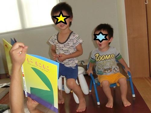 絵本の「もこもこ」を読む3歳と2歳の子ども