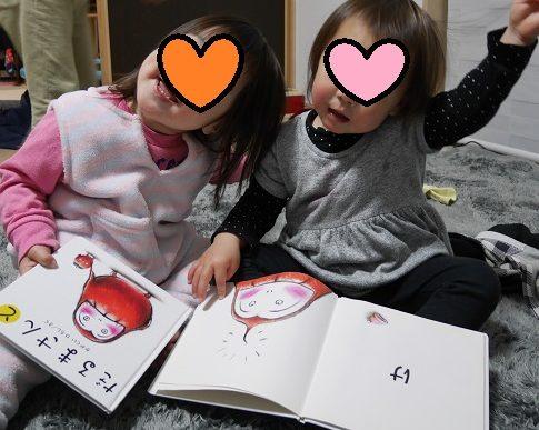 「だるまさんが」の絵本を読んで、自分の「け」を持ち上げる1歳女の子