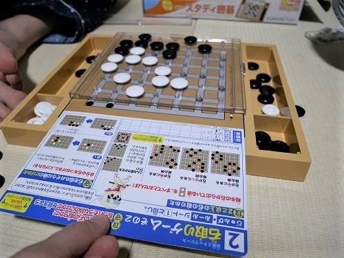 スタディ囲碁の対戦ステップシートを、盤上のすき間にさしこんでいるところ