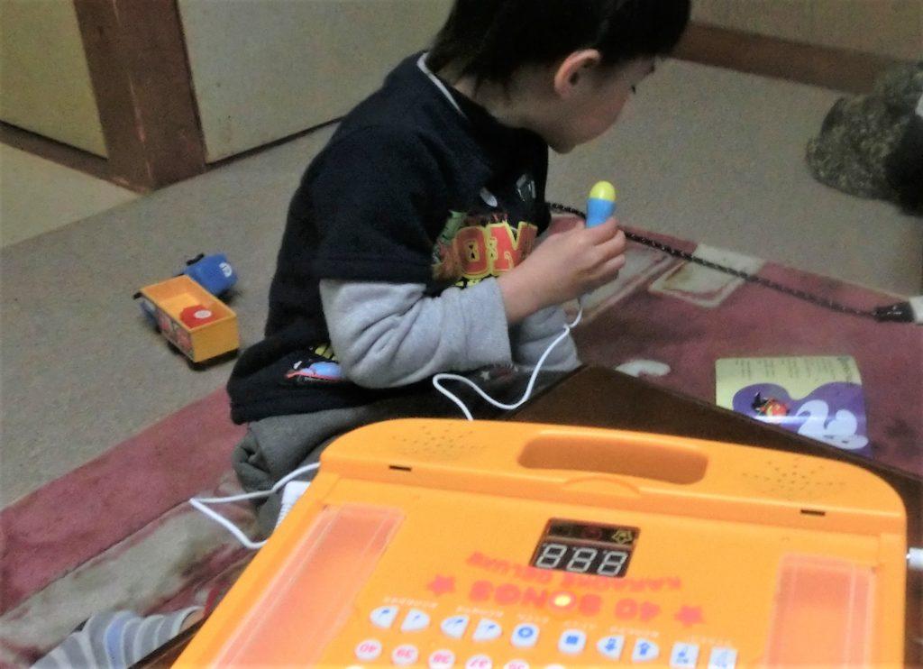 カラオケのおうた絵本おもちゃで歌う3歳男の子