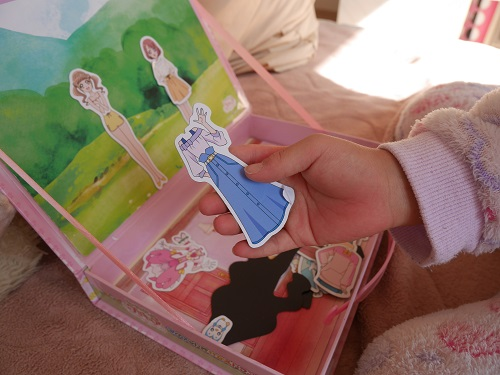 マグネットの着せ替え絵本の人形の洋服を手に持っているところ