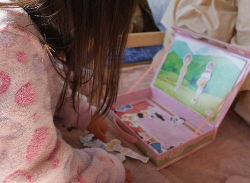 プリキュアのマグネット着せ替え絵本で遊んでいる4歳女の子