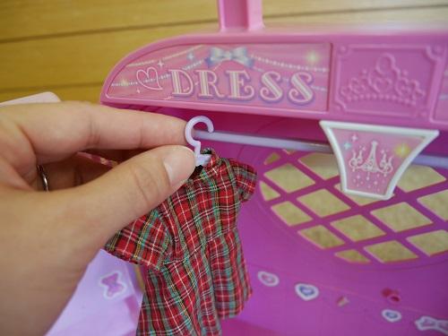 リカちゃんの服をハンガーに入れ、それをフックにかける作業