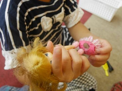 マキちゃん人形にスカートをはかせようとしている女の子