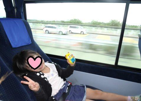 空港まで、高速バスで移動中におもちゃで遊ぶ5歳の女の子