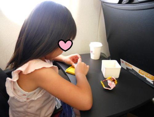 飛行機の座席でラキューで遊んでいる5歳の女の子