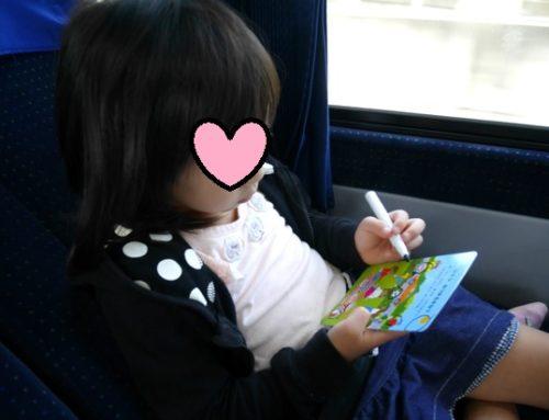 バスや新幹線の移動中に、ホワイトボードペンのお絵かきで暇つぶしをしている5歳の女の子