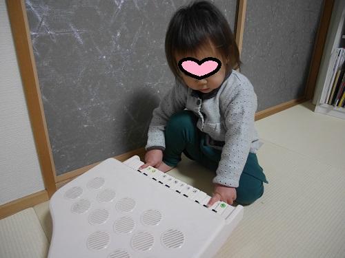 ピアノのおもちゃを弾く2才児