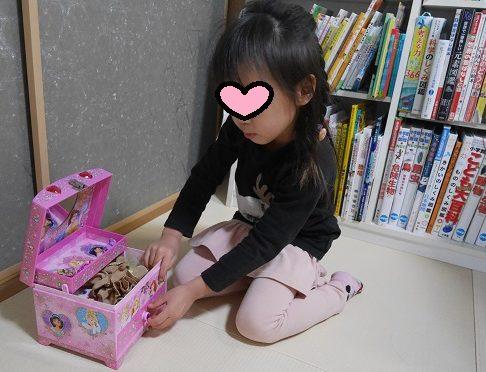 アクセサリーケースにシュシュをしまっている5歳女の子