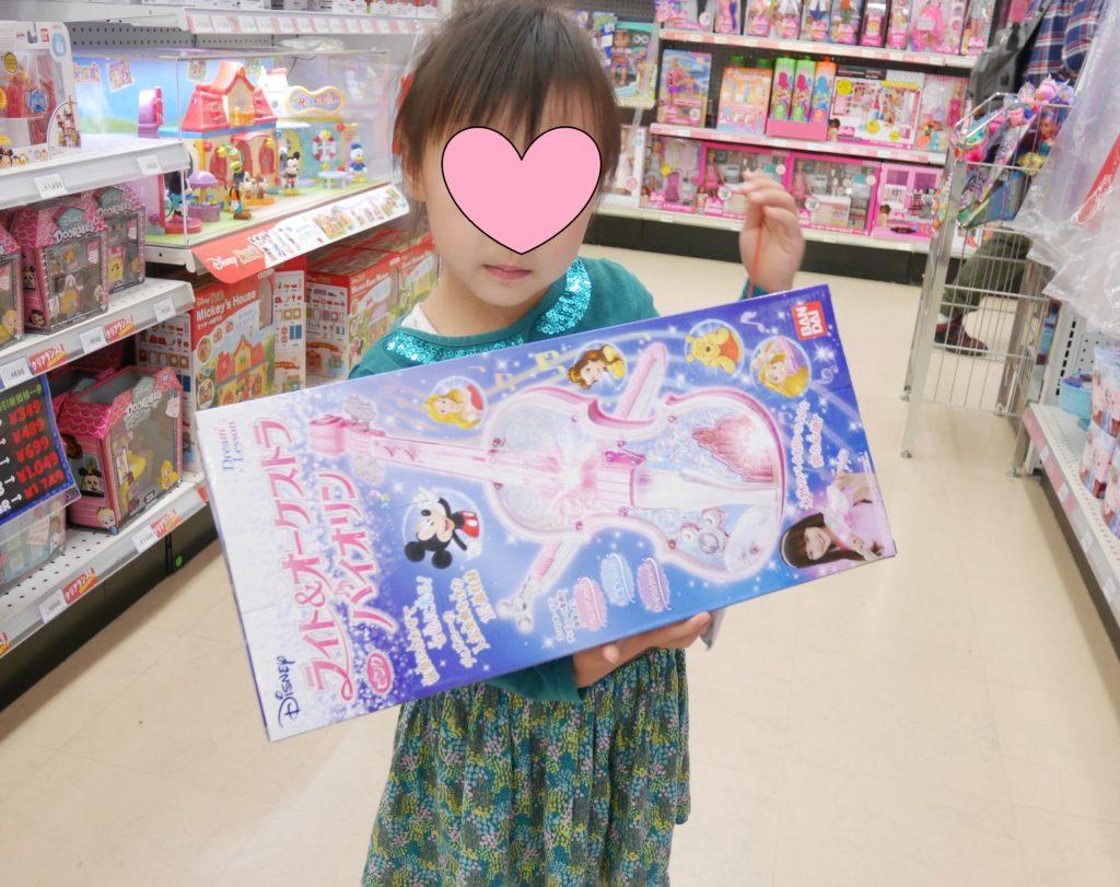 おもちゃ屋さんでディズニーのオーケストラバイオリンを持っている女の子
