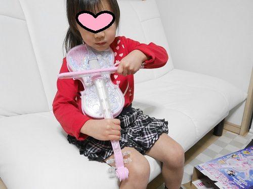 ディズニーのオーケストラバイオリンのピンク色を弾いている4歳女の子