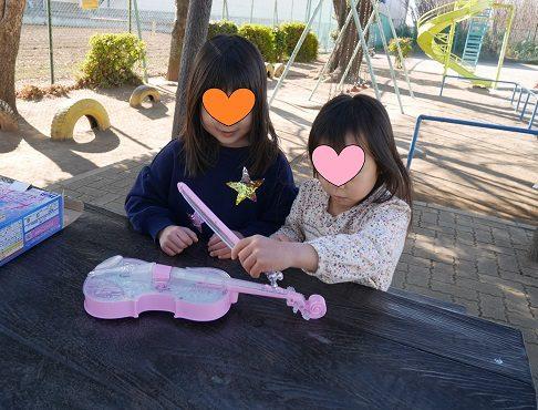 ディズニーのバイオリンのおもちゃを公園で友達と遊ぶ女の子