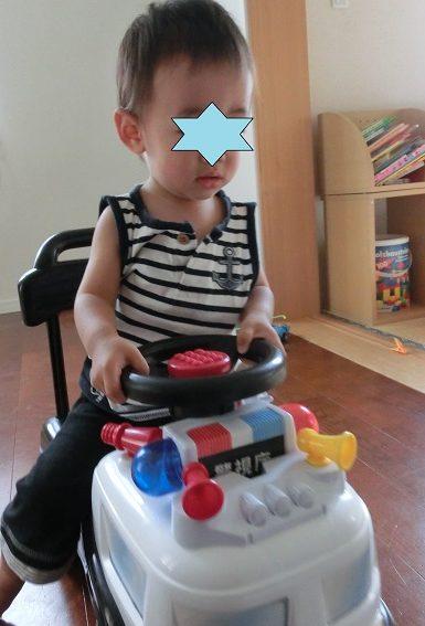パトカーのおもちゃに乗って遊んでいる0歳男の子