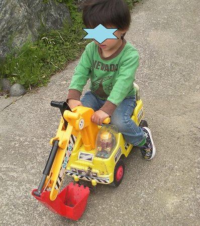 ショベルカーの乗用おもちゃに乗っている2歳の男の子