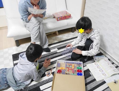 電脳サーキットで遊んでいる大人と小学生の親子