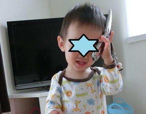 ママの携帯を耳にあてて遊んでいる1歳の男の子