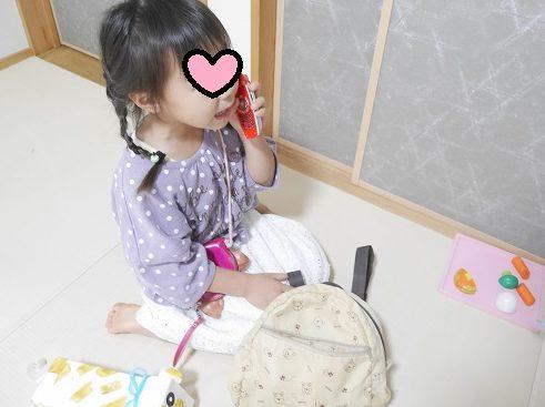 携帯のおもちゃでおはなしをしている4歳女の子