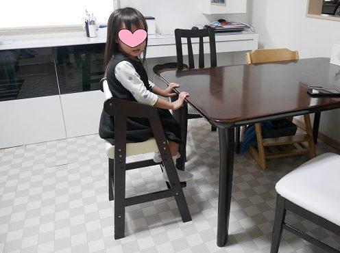 ダイニングテーブルで子供用椅子に座っている4歳女の子